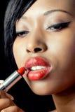Mujer hermosa que aplica el lápiz labial Fotos de archivo