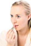Mujer hermosa que aplica el lápiz labial Imagen de archivo libre de regalías