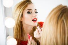 Mujer hermosa que aplica el lápiz labial en el espejo Foto de archivo libre de regalías