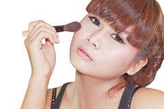 Mujer hermosa que aplica el polvo en mejilla con el cepillo Imagen de archivo