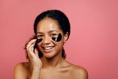 Mujer hermosa que aplica el remiendo del gel en su cara Fotos de archivo libres de regalías