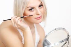 Mujer hermosa que aplica el rimel en las pestañas. Maquillaje del ojo Foto de archivo libre de regalías
