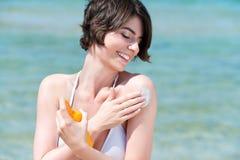 Mujer hermosa que aplica el suncream Foto de archivo libre de regalías