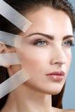 Mujer hermosa que aplica el tratamiento de elevación de la cinta en cara Fotos de archivo libres de regalías