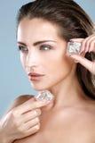 Mujer hermosa que aplica el tratamiento del cubo de hielo en cara Imagen de archivo