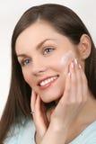 Mujer hermosa que aplica la crema a la cara Imágenes de archivo libres de regalías