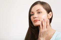 Mujer hermosa que aplica la crema a la cara Fotos de archivo