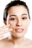 Mujer hermosa que aplica la fundación en cara con los fingeres Imágenes de archivo libres de regalías