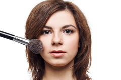 Mujer hermosa que aplica la fundación en su cara Imagen de archivo libre de regalías