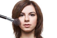 Mujer hermosa que aplica la fundación en su cara Imágenes de archivo libres de regalías