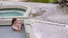 Mujer hermosa que aplica la máscara del fango en cara y piel del cuerpo mientras que toma el baño mineral en centro turístico nat almacen de metraje de vídeo