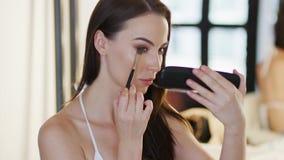 Mujer hermosa que aplica los cosméticos almacen de metraje de vídeo