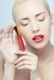Mujer hermosa que aplica lustre del labio Imagenes de archivo