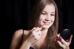 Mujer hermosa que aplica maquillaje Fotos de archivo
