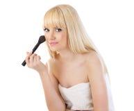 Mujer hermosa que aplica maquillaje con el cepillo Imagen de archivo