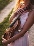 Mujer hermosa que aprende tocar el violín en fondo de la naturaleza Foto de archivo