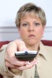 Mujer hermosa que apunta el telecontrol con la luz apagado Imágenes de archivo libres de regalías