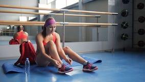 Mujer hermosa que ata cordones en el gimnasio Fotografía de archivo libre de regalías
