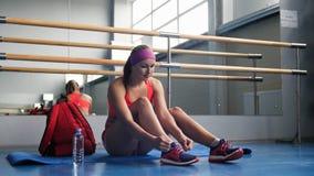 Mujer hermosa que ata cordones en el gimnasio Foto de archivo