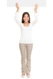 Mujer hermosa que aumenta para arriba una cartelera vacía Foto de archivo