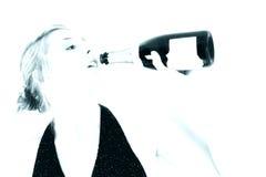 Mujer hermosa que bebe de una botella de Champán Imagen de archivo libre de regalías