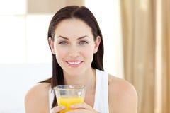 Mujer hermosa que bebe el zumo de naranja Imagenes de archivo