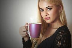 Mujer hermosa que bebe a la muchacha de Coffee.Blond con la taza de té Fotos de archivo