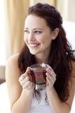 Mujer hermosa que bebe una taza de té en cama Imagen de archivo libre de regalías