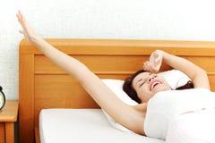 Mujer hermosa que bosteza y que estira en cama. Foto de archivo libre de regalías