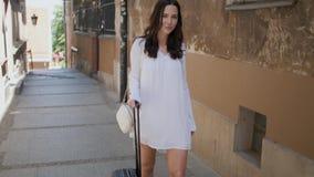 Mujer hermosa que camina con la maleta de la carretilla en pequeña calle en la ciudad metrajes