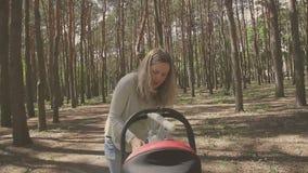 Mujer hermosa que camina con su pequeña hija y que empuja el cochecito en parque almacen de video