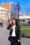 Mujer hermosa que camina en ciudad y chaqueta de cuero que lleva Imagen de archivo libre de regalías