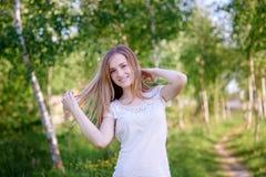 Mujer hermosa que camina en hierba en arboleda del abedul en el día de verano Fotografía de archivo