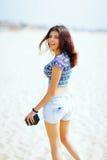 Mujer hermosa que camina en la playa con la cámara retra Foto de archivo libre de regalías