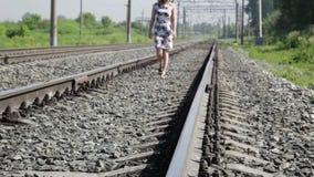 Mujer hermosa que camina a lo largo de pistas ferroviarias en un día del sol almacen de video