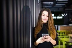 Mujer hermosa que charla en el teléfono móvil, hembra joven en buen mensaje de texto de la lectura del humor en el teléfono de cé Imagenes de archivo