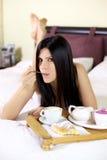 Mujer hermosa que come con la cuchara en cama Fotografía de archivo libre de regalías