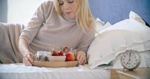 Mujer hermosa que come el desayuno con el yogur, la fruta y los cereales en cama La mañana despierta en casa en dormitorio caucás metrajes