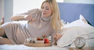 Mujer hermosa que come el desayuno con el yogur, la fruta y los cereales en cama La mañana despierta en casa en dormitorio caucás almacen de video