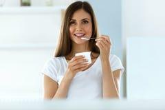 Mujer hermosa que come el yogur orgánico Nutrición de la dieta sana imagen de archivo