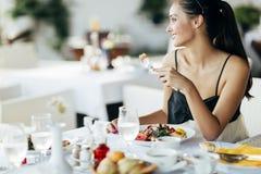 Mujer hermosa que come la comida en restaurante foto de archivo