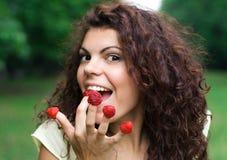 Mujer hermosa que come la frambuesa fresca Fotos de archivo