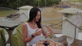 Mujer hermosa que come la pizza en la terraza de un restaurante almacen de video