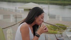 Mujer hermosa que come la pizza en la terraza de un restaurante almacen de metraje de vídeo