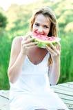 Mujer hermosa que come la sandía en el parque Fotografía de archivo
