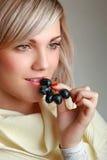 Mujer hermosa que come la uva fresca Fotografía de archivo