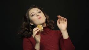 Mujer hermosa que come los alimentos de preparación rápida, tiroteo del primer almacen de video