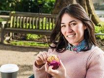 Mujer hermosa que come un mollete afuera en la cafetería Fotos de archivo