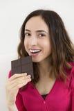 Mujer hermosa que come una barra de chocolate oscura Fotos de archivo