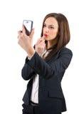 Mujer hermosa que compone usando su teléfono como un espejo aislado Fotografía de archivo